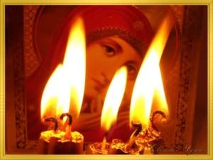 Икона Божьей Матери на фоне горящих свечей